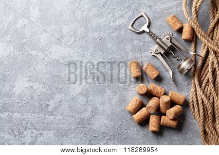 Wine corks and corkscrew over stone background. Top view with copy space