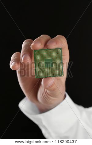 Male hand holding microprocessor on black background