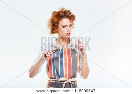 Young housewife holding sharp knife isolated on a white background