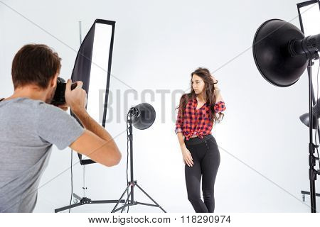 Photographer shooting model in professional studio with softboxes