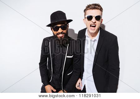 Two irritated modern young men in black suits shouting and looking at camera over white background