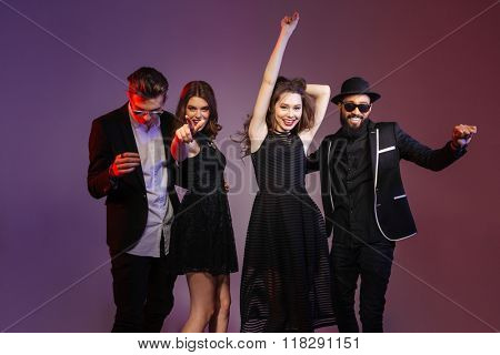 Muliethnic group of happy young people dacing over purple background