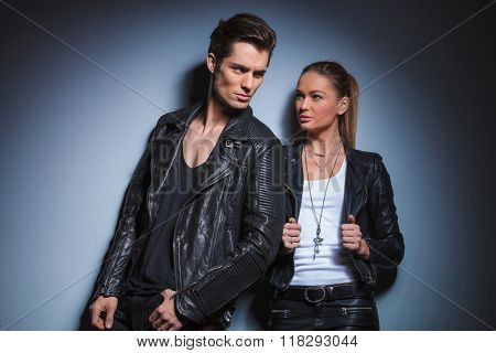 sexy biker pose looking away while his woman is starring at him arranging her leather jacket in studio background