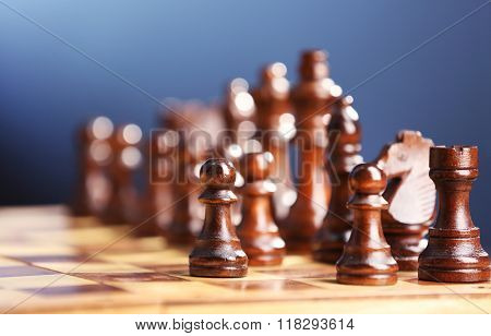 Chess pieces and game board on dark blue background