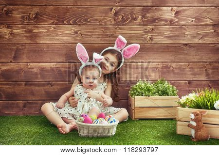 Happy Easter! Cute little children girls wearing bunny ears on Easter day. Sisters hunting for Easter eggs on the lawn near the house. Girls having fun, playing and hugging.