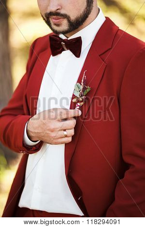 Boutonniere geared to buttonhole. Groom in red suit with stylish beard and mustache.