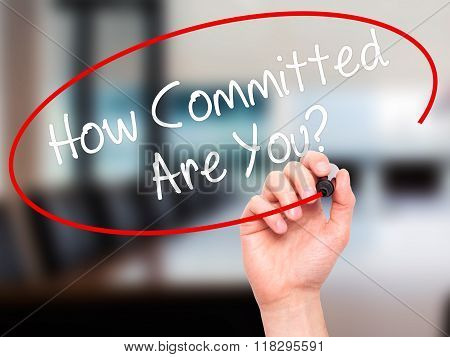 Man Hand Writing How Committed Are You? With Black Marker On Visual Screen