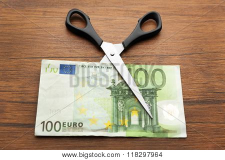 Concept of spending money - scissors cut money on wooden background