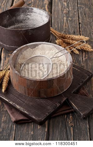 Flour In A Wooden Bowl With Sieve On Vintage Board