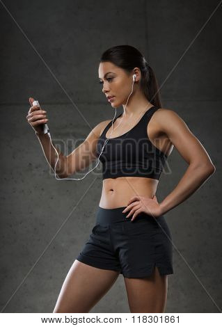 sport, fitness, technology and people concept - young woman with smartphone and earphones listening to music in gym