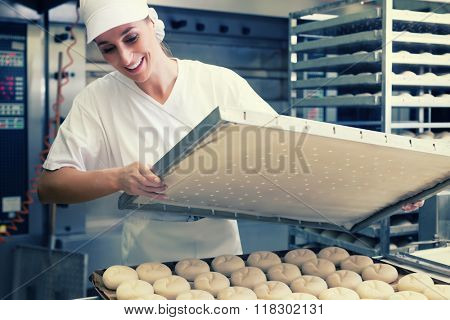Baker woman with sheet of bread in bakery baking in oven, filtered image