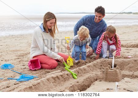 Family Building Sandcastles On Beach Together