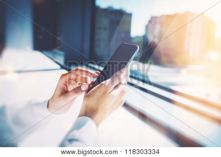 Girl touching a screen of her smarthone. Blurred background, horizontal