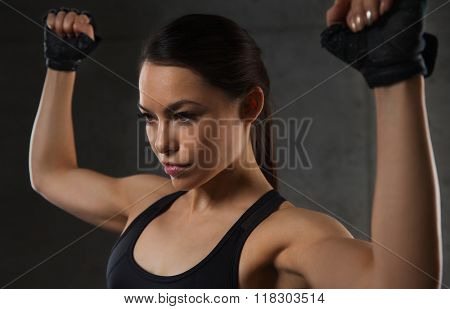 sport, fitness, bodybuilding, weightlifting and people concept - young woman flexing muscles in gym