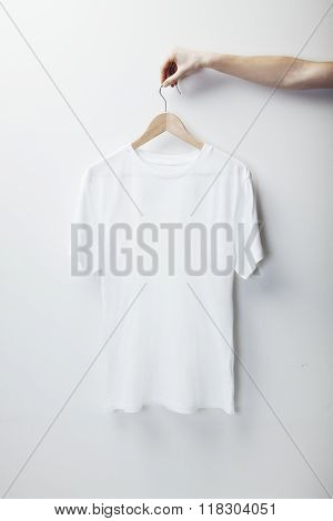 Photo of white tshirt hanging female hand
