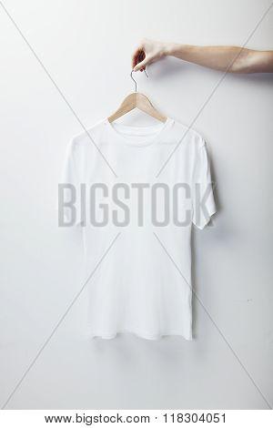 Photo of white tshirt hanging female hand