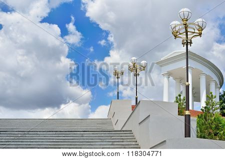Large Staircase With A Colonnade On Background Of Blue Sky