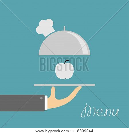 Hand Holding Silver Platter Cloche With Chefs Hat And Apple. Menu Card. Blue Background. Flat Design