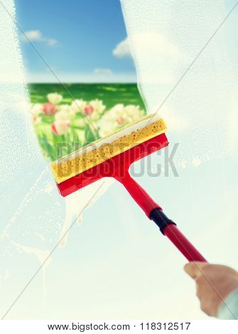 people, housework and housekeeping concept -close up of hand cleaning window glass with sponge mop and foam over blue sky and flower field background