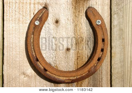 Lucky Horse Shoe On A Wooden Background.