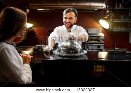 Chef cook serving dish to the client