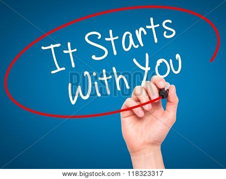 Man Hand Writing It Starts With You With Black Marker On Visual Screen