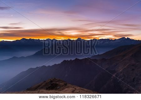 Mountain Silhouette And Stunning Sky With Moon At Sunset