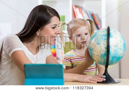 Pretty woman teaching and showing globe to kid