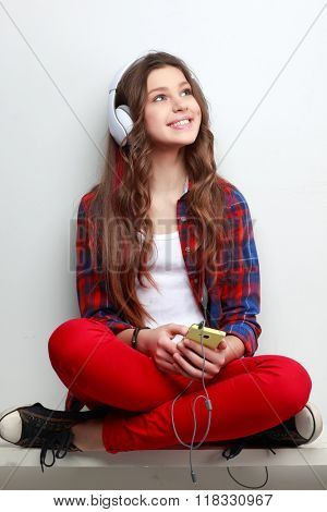 Beautiful young long-haired girl with headphones and telephone, listening music