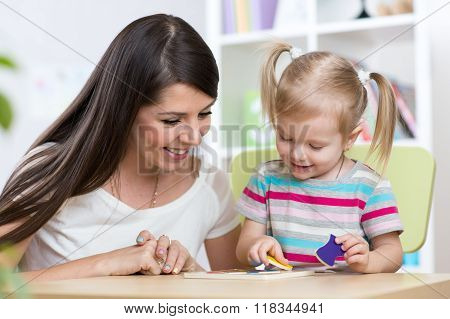 Little girl is solving puzzle. Mother watching at her actions