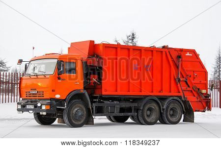 NOVYY URENGOY RUSSIA - JANUARY 28 2016: Orange KAMAZ 65115 (KO-427) garbage truck at the city street.