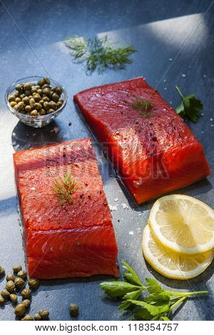 Two pieces of raw wild salmon fish steaks with lemon, capers and herbs, ready to cook