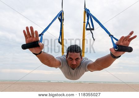 Indian ethnicity young man wit a strong body doing yoga exercises or fly-yoga on the sea background