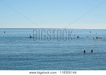 People Swimming And Rowing In Sea