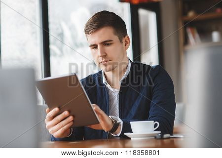 Handsome Man Drinking Coffee And Using Tablet Computer Inside Cafe Bar.