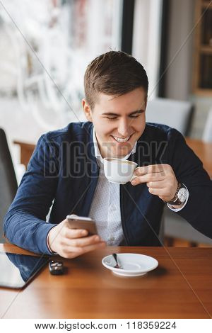 Handsome man having coffee and using smartphone at coffee shop