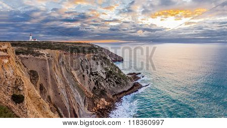 The Espichel Cape, with the 18th century lighthouse and a view over the Atlantic Ocean during sunset. Sesimbra, Portugal.
