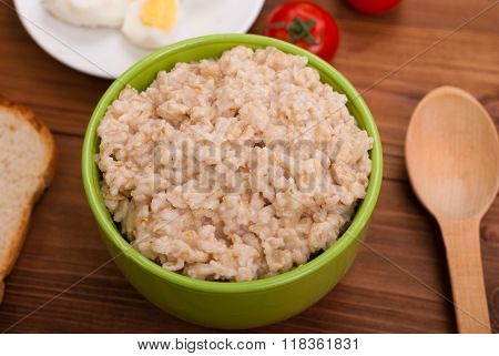 Oatmeal In A Bowl On The Wooden Table.