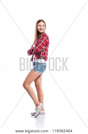 Girl in shorts and checked shirt, arms crossed, isolated