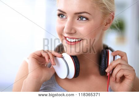 Young beautiful woman at home sitting on sofa and listening music