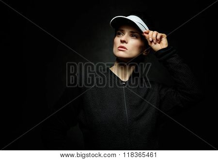 Portrait Of Fit Woman Looking Aside Against Black Background
