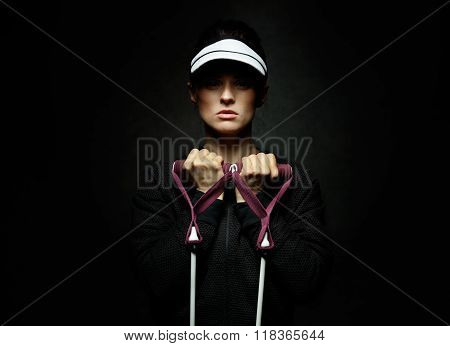 Young Fit Woman Holding Resistance Band Against Black Background