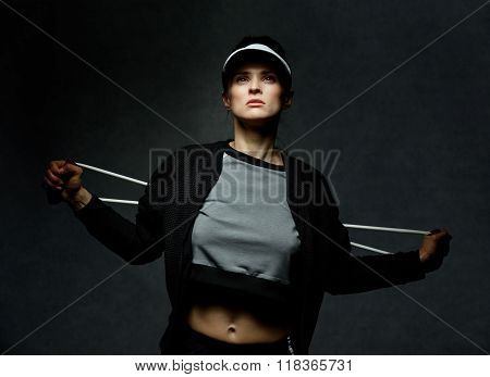 Fit Woman Training With Resistance Band Against Dark Background