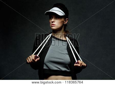 Young Fit Woman Holding Resistance Band Against Dark Background