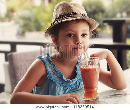 Fun Kid Girl In Fashion Hat Drinking Smoothie Juice In Street Restaurant. Toned Closeup Portrait