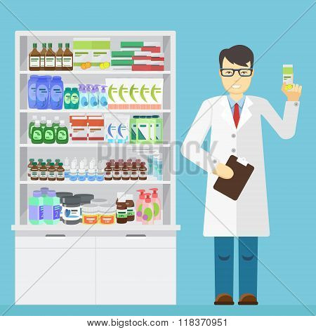 Male pharmacist holding in the hands of the medication in a pharmacy near shelves with medications.
