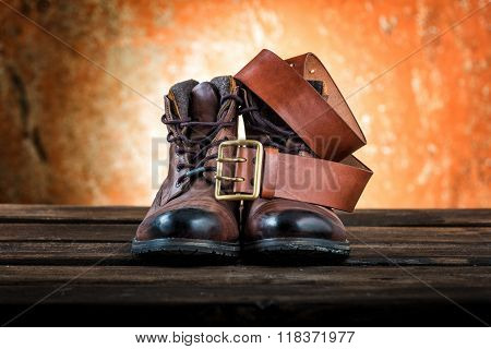 Brown winter boots and leather belt with buckle, wooden background