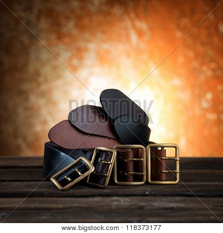 Different belts with buckle on rusty wooden background