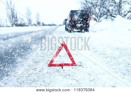 Car on winter road and warning triangle