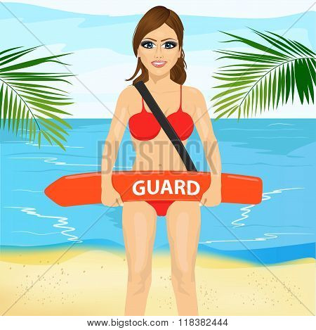 Young female lifeguard holding float lifesaver equipment